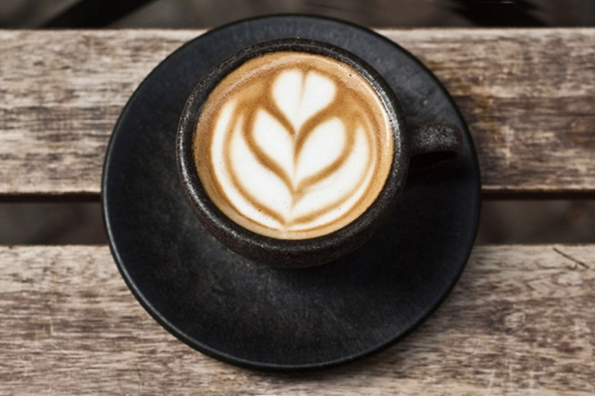 Picture of an espresso cup on a bench with latte art in a flower shape)