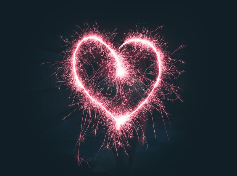 photo of a sparkler being used to draw a heart in the air